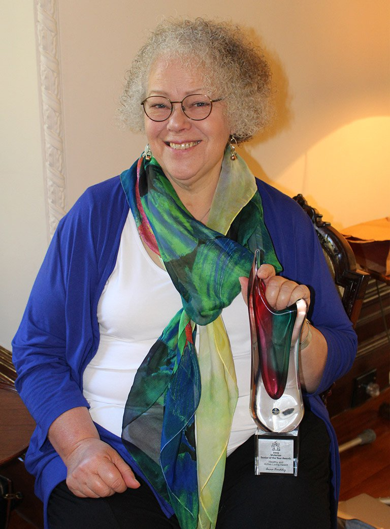 Photo of a smiling woman with short, curly grey hair, wearing a bright scarf and holding a trophy in the form of a sculptural and brightly coloured glass vase.