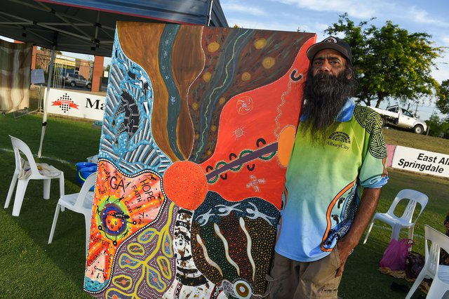 An Indigenous Elder wearing a black cap and blue and green polo shirt standing next to Indigenous artwork, outdoors on green grass and blue sky behind.