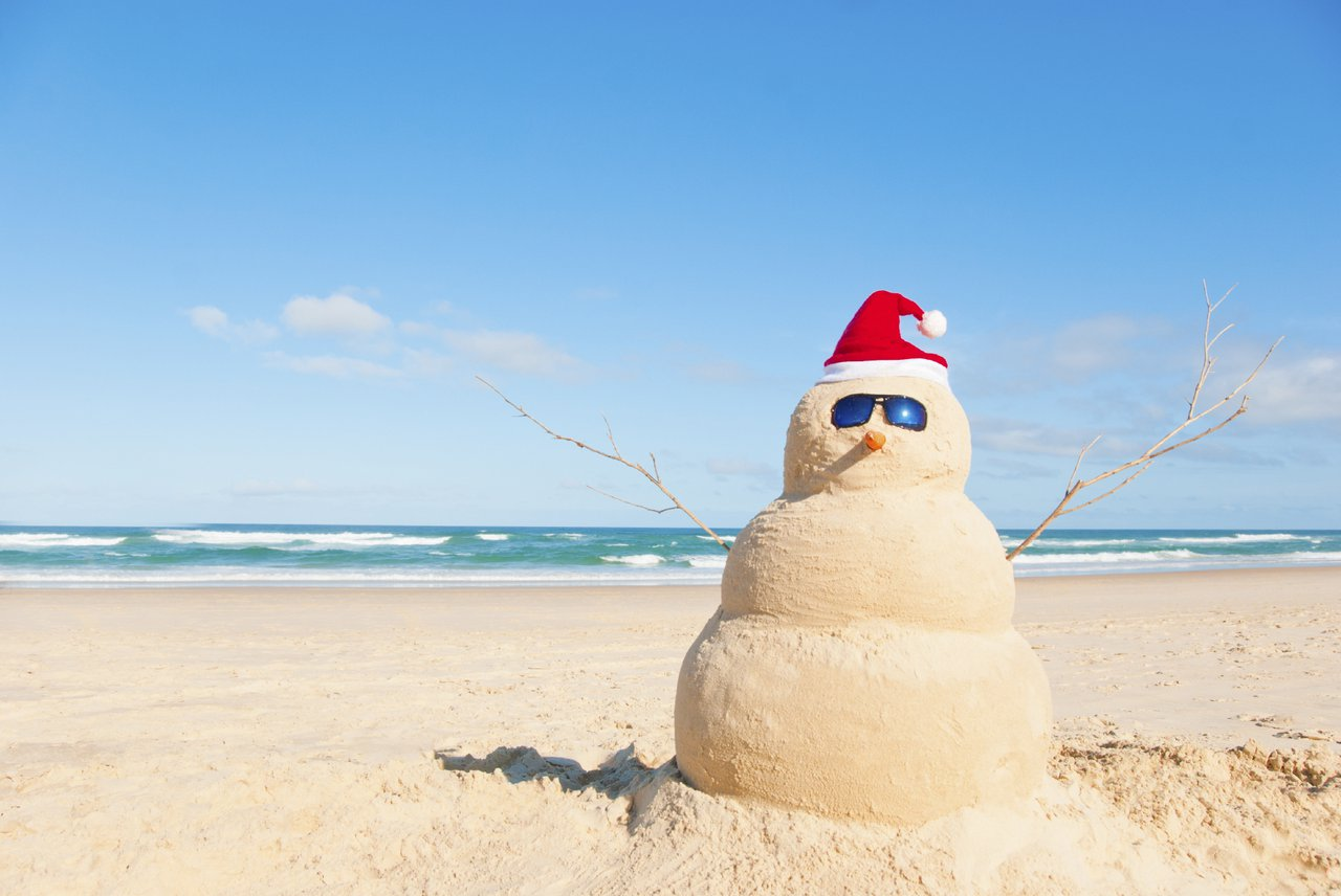 Close up of a beach sand snowman with a santa hat