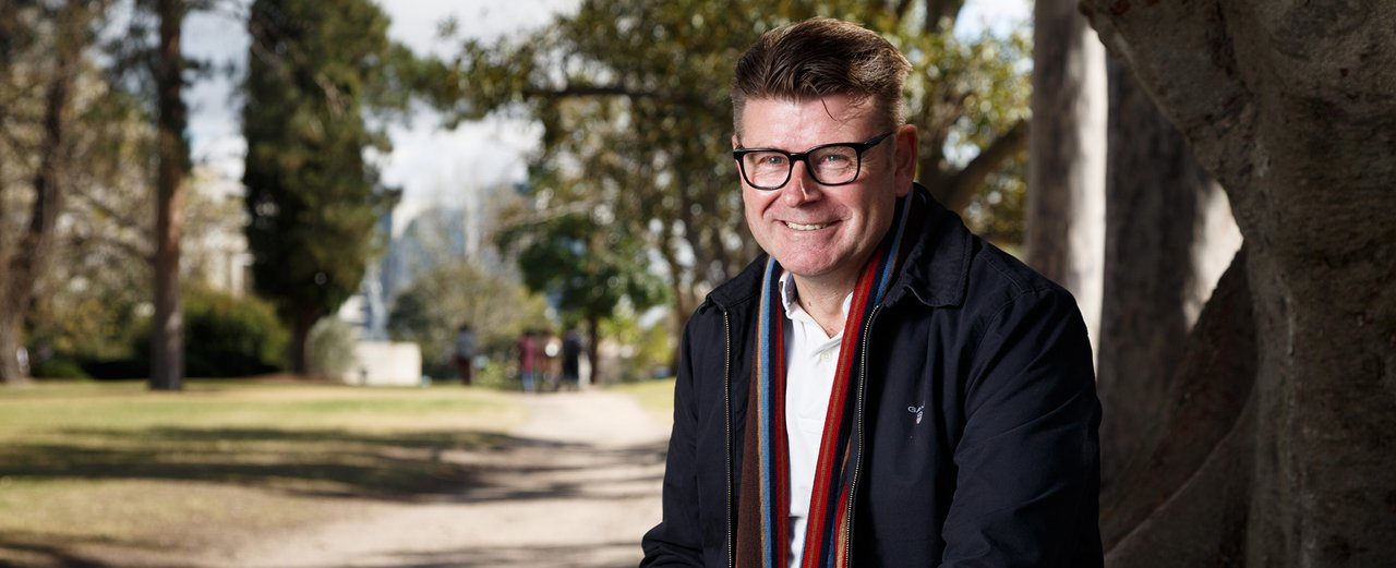 Photo of a smiling middle-aged man with short brown hair, wearing glasses, a white polo shirt, navy jacket and red scarf, sitting against a tree, parklands behind.