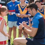 Western Bulldogs captain Easton Wood signing memorabilia for his young fans.