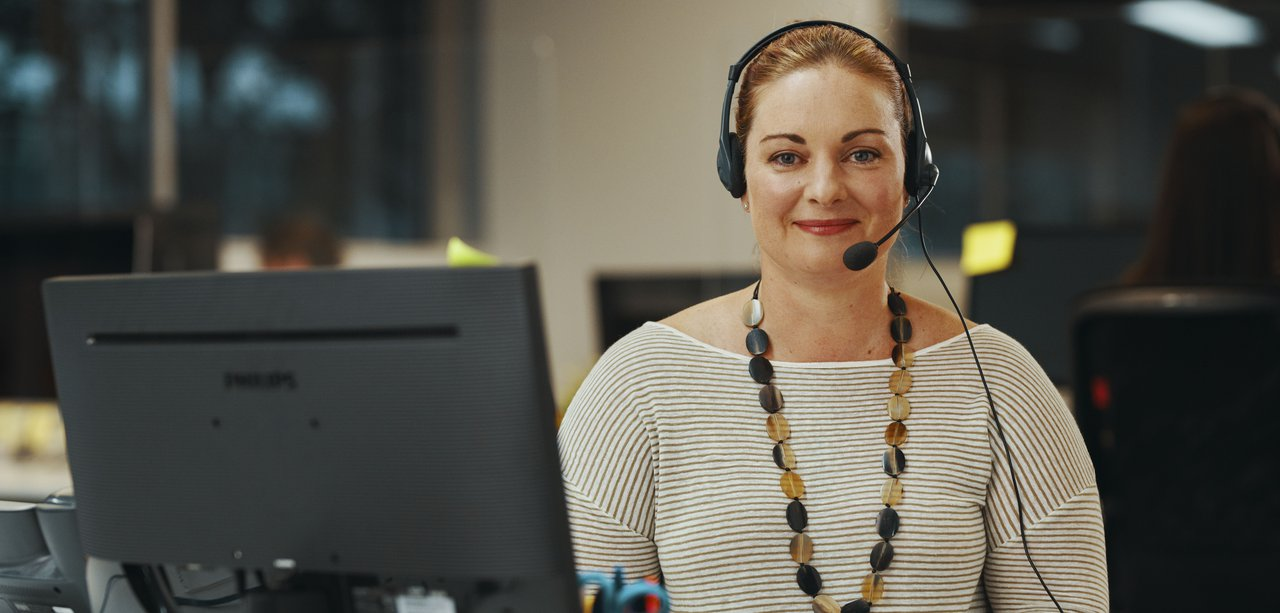 A woman with a headset in front of a monitor