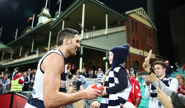 Geelong Cats' Harry Taylor passing a footy ball to a young girl