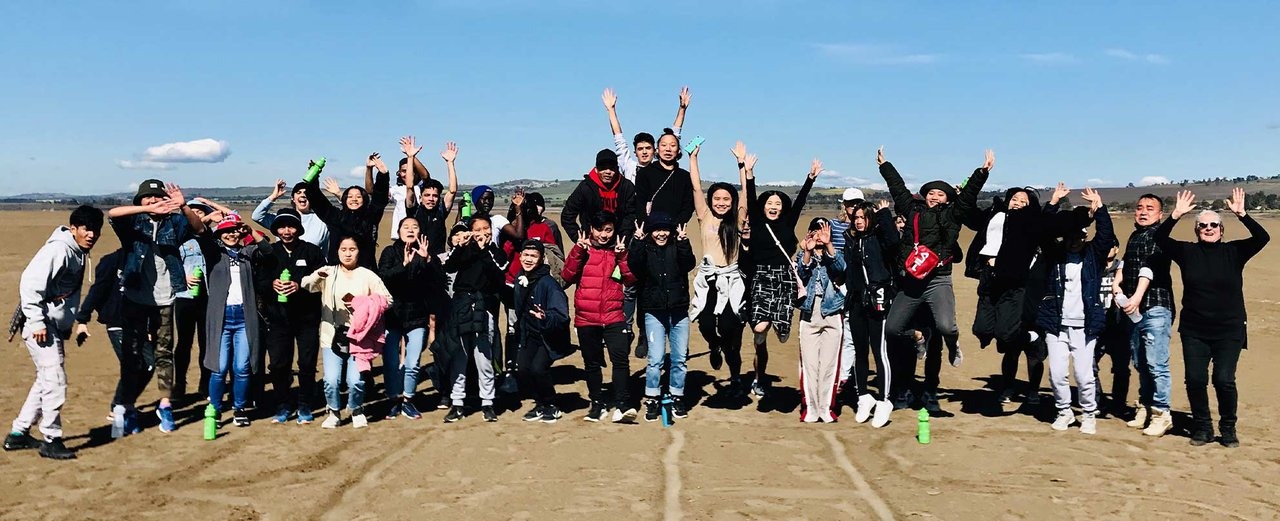 Photo of a large group of young Karen people standing in a wide row on a large expanse of sand, smiling and waving at the camera, some posing and jumping, a middle-aged woman standing and on the end at the right, also smiling and waving, hills and blue sk