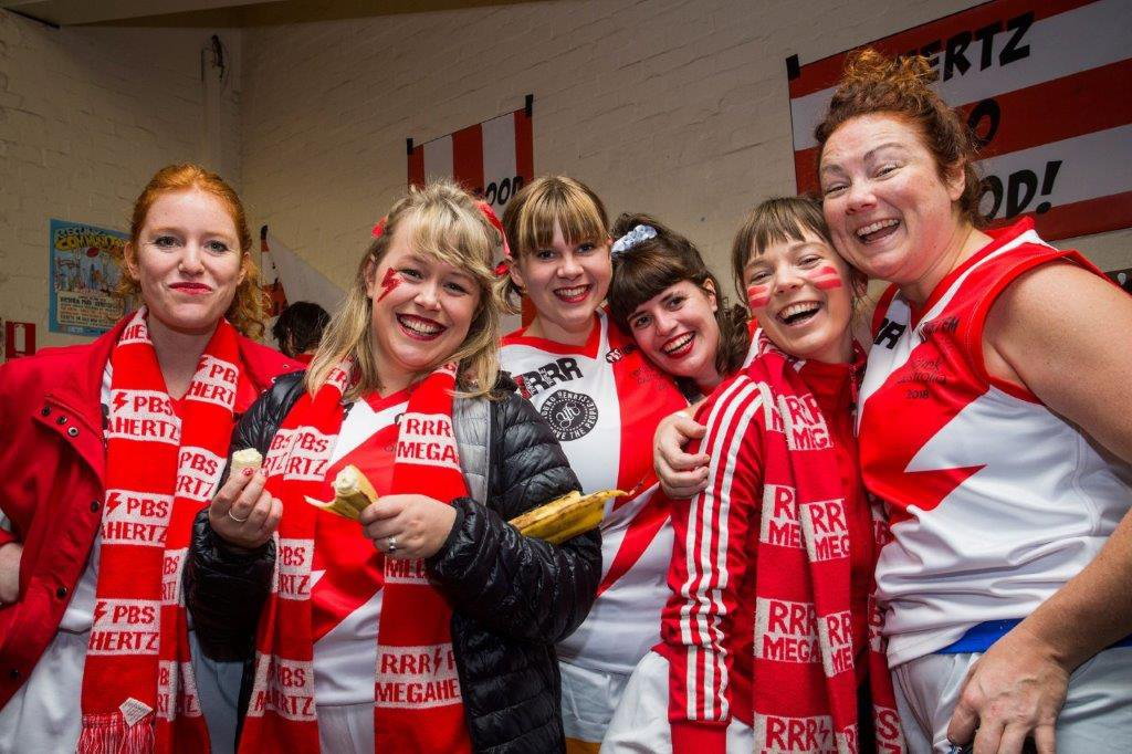 A group of six smiling women inside a sporting club room, all are wearing red and white football uniforms