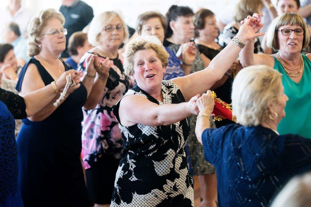 A smiling older woman, hands joined with other women, dancing
