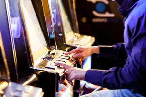Two hands on the buttons of a pokie machine