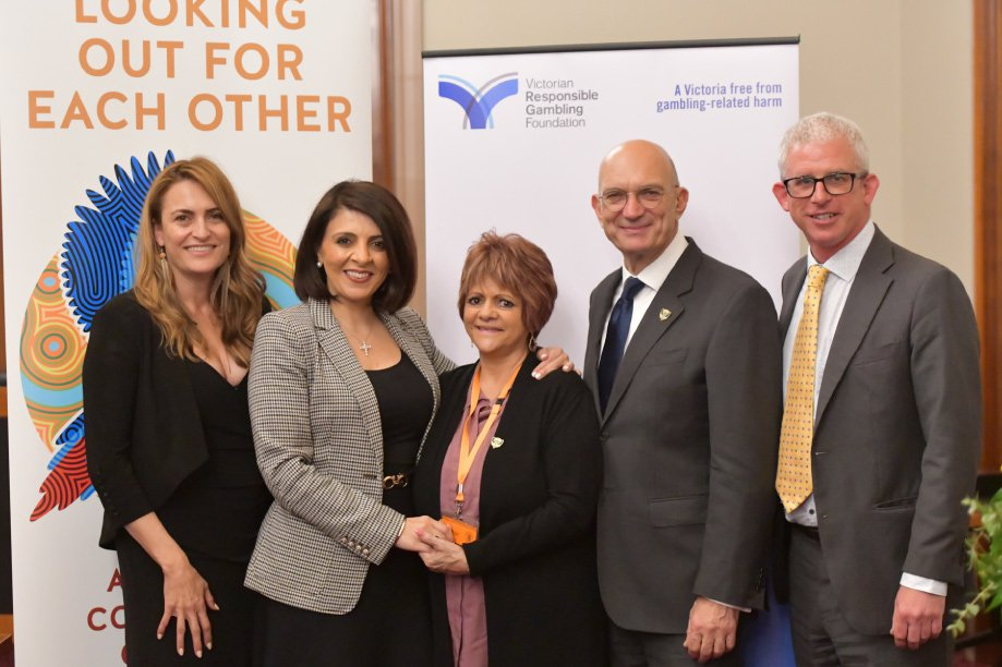 Group photo of three women and two men standing in front of two banners: one that says 'Looking out for each other' and one with the Victorian Responsible Gambling Foundation logo and the tagline: A Victoria free from gambling-related harm