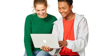 Two young male and female student looking at a laptop screen and smiling