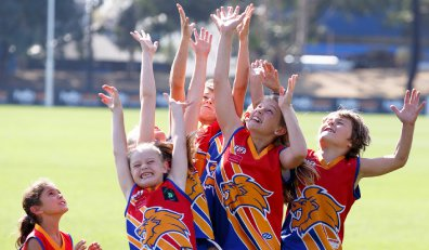 Photo of a group of girls in AFL guernseys on an oval jumping for a football.