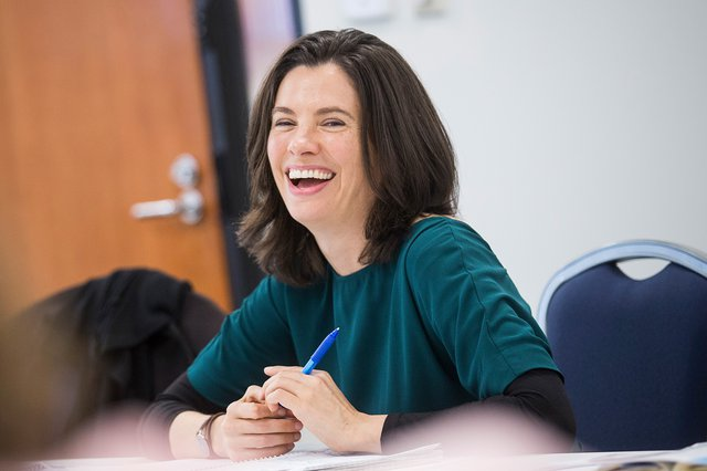 Photo of a smiling woman with long dark hair, sitting at a meeting table with papers on it, a pen in her hand.