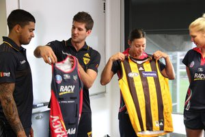 Melbourne Vixens players and Hawthorn Hawks swapping shirts