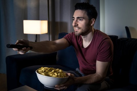 A young male sitting on a couch holding a bowl of chips in one hand and a remote in the other hand