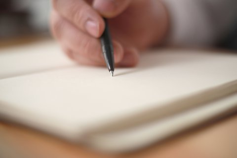 Close up of a male writing in a notebook