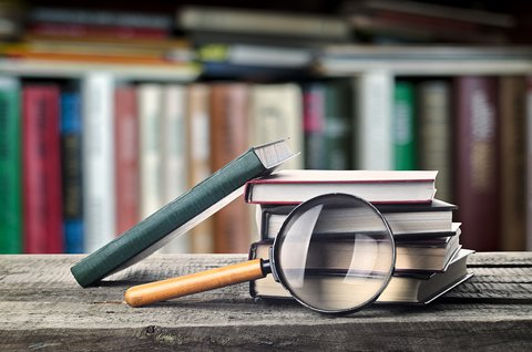 Stack of books and magnifier on wooden table with bookshelf in the background
