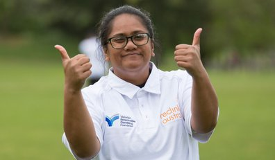 A woman in a white cricket shirt with the Victorian Responsible Gambling Foundation logo and the Reclink Australia logo on it, giving the thumbs up, a cricket oval in the background.