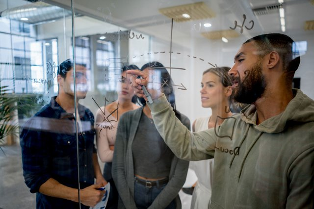 A male writing ideas on a glass board at an office and explaining it to a group of four